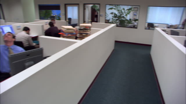 medium shot walking point of view boss walking through office and looking at employees idling in cubicles / low angle - dejaover点の映像素材/bロール