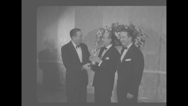 walt disney presents award to jack warner as ralph w russell stands by / medium shot rosalind russell presents award to tab hunter for most promising... - disney stock videos and b-roll footage