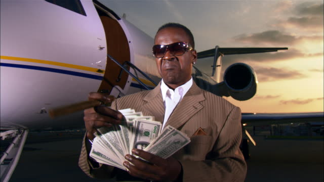medium shot wealthy businessman counting money and holding cigar near private airplane / long beach, california, usa - sigaro video stock e b–roll