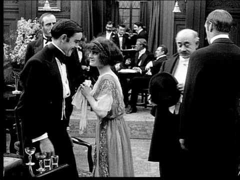 1914 b/w medium shot wealthy man shaking hands and talking with woman at party before she leaves - party social event stock videos & royalty-free footage
