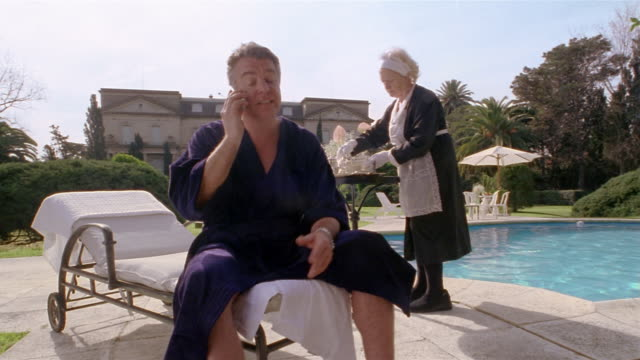 Medium shot wealthy man talking on cell phone on pool deck / maid serving him tea