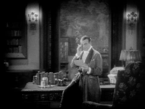 1928 b/w medium shot wealthy man wearing smoking jacket and monocle, smoking cigarette and reading letter in study / usa  - fade out stock videos & royalty-free footage