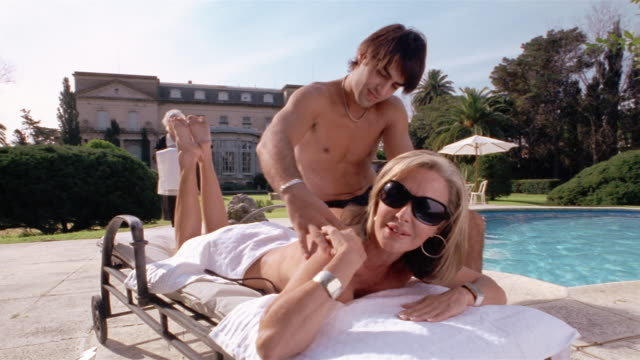 Medium shot wealthy mature woman getting massage from young man on pool deck / maid holding towel in background