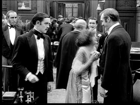 1914 b/w medium shot wealthy men and woman talking and shaking hands at party - formal reception stock videos and b-roll footage
