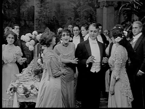 stockvideo's en b-roll-footage met 1909 b/w medium shot wealthy people talking at dinner party  - 19e eeuwse stijl