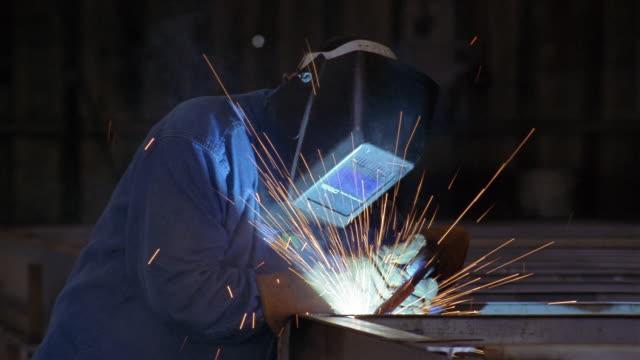 vídeos de stock, filmes e b-roll de medium shot welder wearing mask and working in factory - soldar