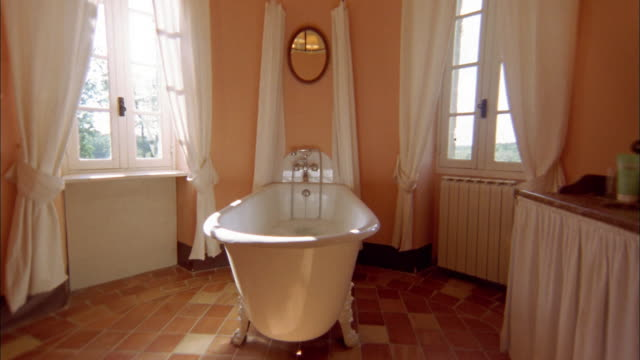 medium shot white bathtub on tile floors w/windows in background - tile stock videos & royalty-free footage