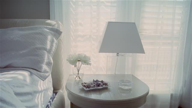 Medium shot white nightstand with lamp and flowers/ Solebury, Pennsylvania