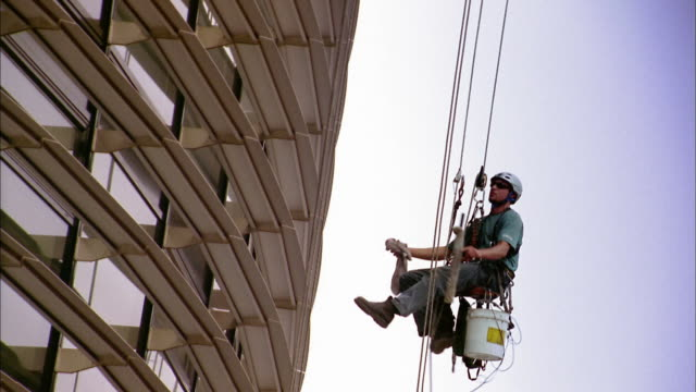 medium shot window washer on harness cleaning window w/squeegee and bucket - window washer stock videos & royalty-free footage