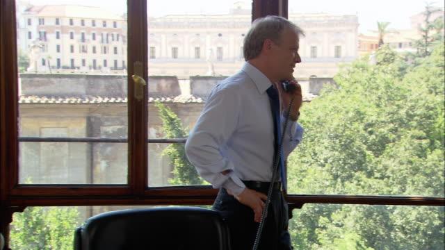 medium shot window with view of old buildings/ businessman on phone walking on camera/ pan man on phone pacing/ rome - anwalt stock-videos und b-roll-filmmaterial