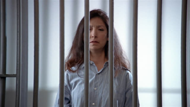 medium shot woman against white background looking at camera/ prison door closes on her/ woman holding prison bars - prison bars stock videos and b-roll footage