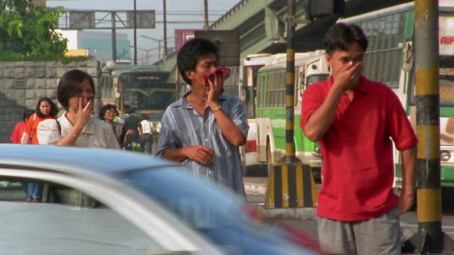 medium shot woman and 2 men covering their noses + mouths with handkerchiefs while waiting to cross intersection - indonesia street stock videos & royalty-free footage