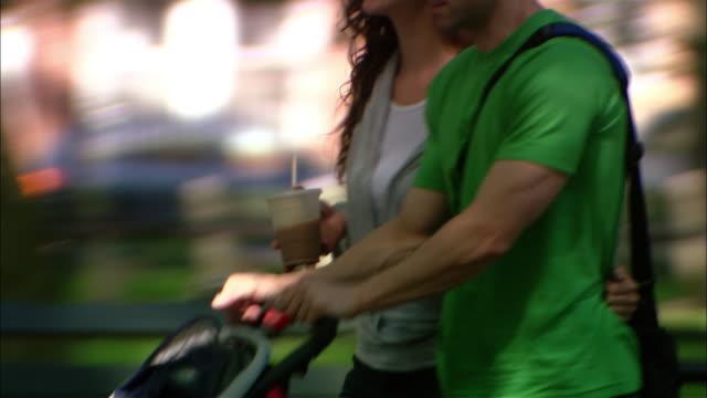 Medium shot woman and man pushing stroller walking in park / tilt down baby in stroller