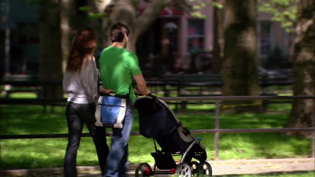 medium shot woman and man pushing stroller walking together in park - pushchair stock videos & royalty-free footage