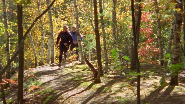 Medium shot woman and man trail running through woods / passing CAM / Bradbury Mountain, Maine