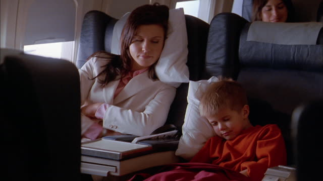 Medium shot woman and young boy sleeping on airplane / woman pulling blanket around boy