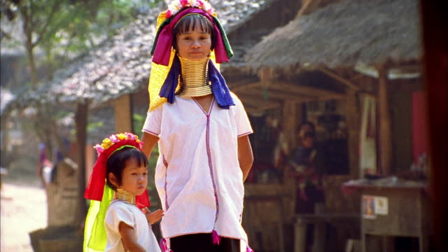 Medium shot woman and young girl of Long-necked Karen Tribe (Padaung) with neck rings / Thailand