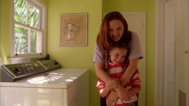 medium shot woman and young girl smiling at cam in laundry room - laundry stock videos & royalty-free footage