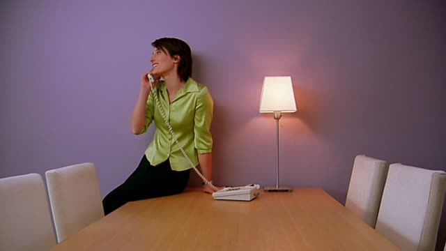 Medium shot woman answering phone in empty conference room / talking / hanging up