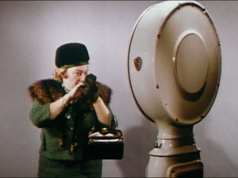 1966 medium shot woman applying makeup in hand mirror / stepping on scales / audio - 毛皮のコート点の映像素材/bロール