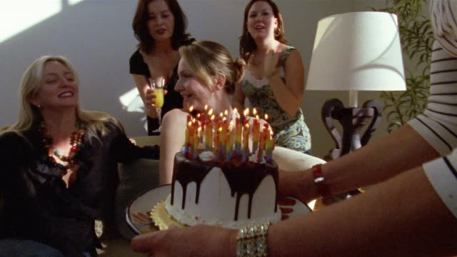 Medium shot woman blowing out candles on birthday cake/ San Francisco, California