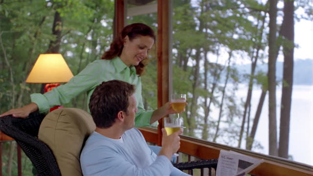 Medium shot woman bringing drinks to man reading newspaper in lakehouse / toasting and looking at view of lake