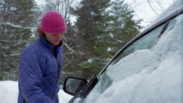 Medium shot woman brushing snow off car window / scraping ice off car window Vermont