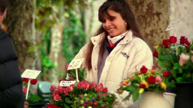 Medium shot woman buying flowers from vendor outdoors / Provence, France