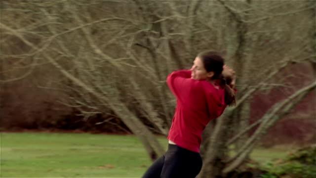 vidéos et rushes de medium shot woman catching and throwing football as dogs walk around/ maine - ball