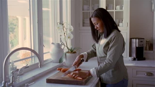 vídeos y material grabado en eventos de stock de medium shot woman chopping carrots near kitchen sink/ solebury, pennsylvania - picar preparar comida