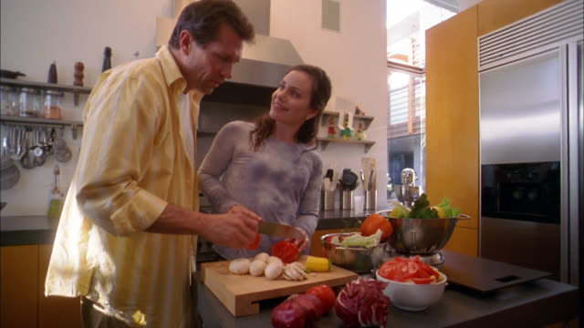 Medium shot woman chopping vegetables on cutting board in kitchen / man talking and eating slices