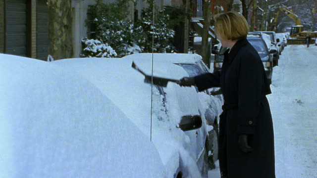 Medium shot woman cleaning snow off car windshield on city street