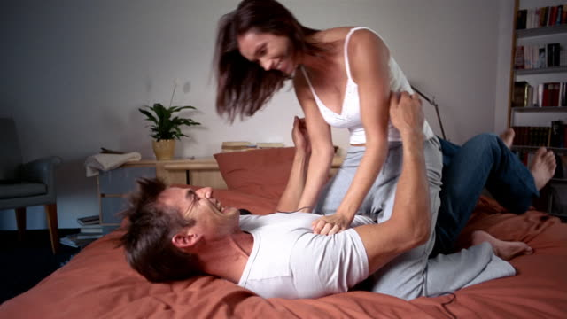 medium shot woman climbing on top of man lying on bed / taking headphones off and hugging him / south africa - legs apart stock videos & royalty-free footage