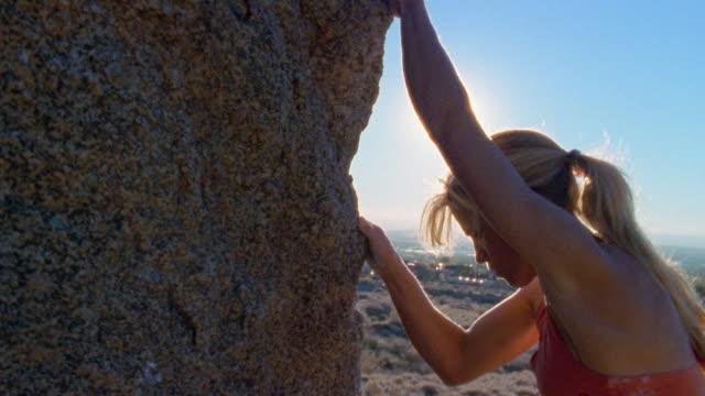 vidéos et rushes de medium shot woman climbing rock / new mexico - effort