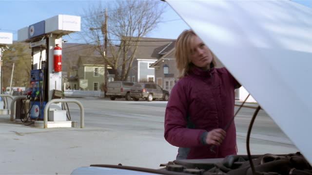 medium shot woman closing hood of car at gas station - hood clothing stock videos and b-roll footage