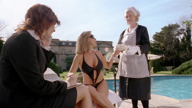 medium shot woman drinking tea and dictating to assistant on pool deck/ giving cup to maid/ taking cell call - stately home stock videos & royalty-free footage