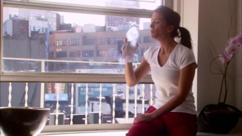 vídeos y material grabado en eventos de stock de medium shot woman drinking water and using bottle to cool herself off by window / nyc - calor