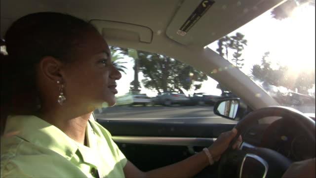 Medium shot woman driving on freeway/ Los Angeles, California