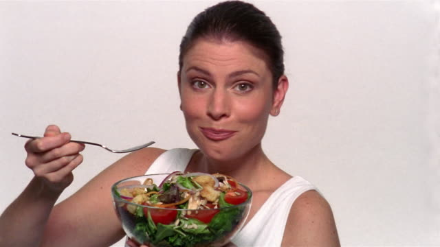 vídeos y material grabado en eventos de stock de medium shot woman eating salad from a bowl / smiling at camera - ensalada