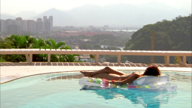 Medium shot woman floating on raft in swimming pool w/skyline in background