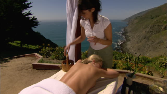 Medium shot woman getting hot stone treatment with ocean in background/ Monterey County, California