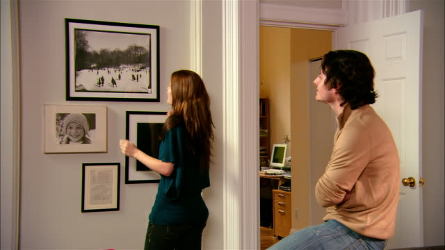 medium shot woman hanging picture and checking it with level/ man embracing woman/ brooklyn, new york - home decor stock videos & royalty-free footage