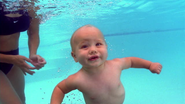 Medium shot woman helping baby swim to surface of water in swimming pool