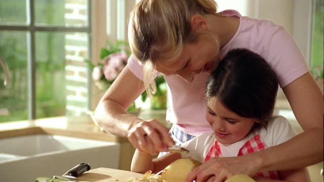 stockvideo's en b-roll-footage met medium shot woman helping girl to peel potato / belgium - schil