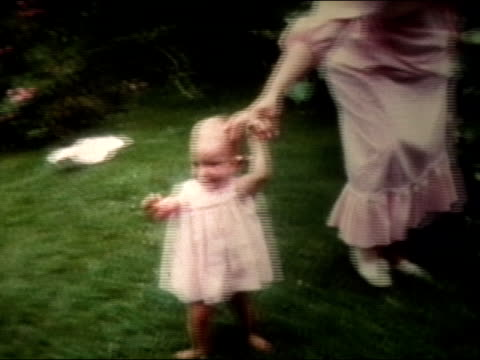 1972 medium shot woman holding baby's hand as baby walks on grass - balance stock videos & royalty-free footage