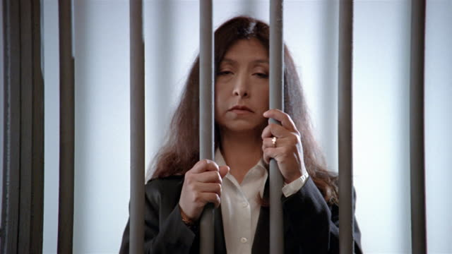 medium shot woman holding prison bars and looking at camera/ woman looking down - colpevolezza video stock e b–roll