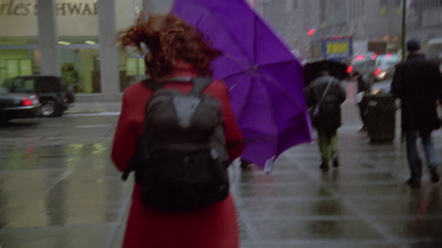 Medium shot woman holding umbrella against wind while walking on sidewalk / New York City