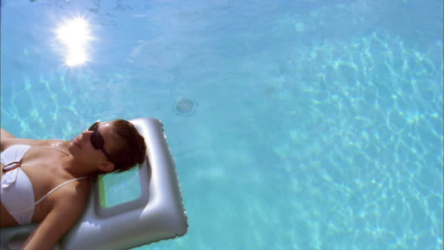 Medium shot woman in bathing suit lounging on raft in pool