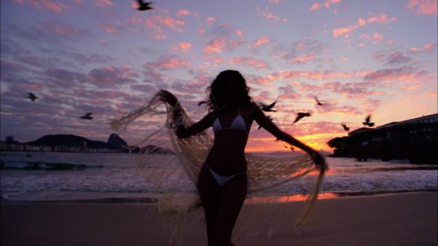 vídeos de stock e filmes b-roll de medium shot woman in bikini dancing w/fringed fabric on beach at sunset - copacabana