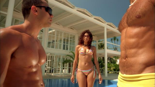 vídeos de stock, filmes e b-roll de medium shot woman in bikini posing and smiling between two barechested men at swimming pool - pelo no peito